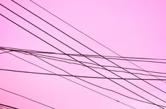 Crossed Wires over a pink background. This pattern of an array of crossed wires combines direction with misdirection Royalty Free Stock Photo