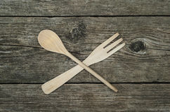 Crossed wooden fork and spoon on rustic background. Crossed wooden fork and spoon on rustic wooden background, top view royalty free stock photography