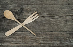 Crossed wooden fork and spoon on rustic background. Crossed wooden fork and spoon on rustic wooden background, top view royalty free stock photo
