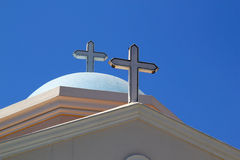 Crosses atop traditional Greek orthodox church on Greek Island. White crosses on top of Greek Orthodox church domes on Greek Island royalty free stock image