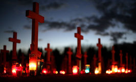 Crosses at cemetery. Flowers and candles at the cemetery at dusk Royalty Free Stock Photo