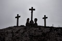 Crosses on the hill. Silhouettes against gloomy sky stock image