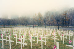 Crosses in the Mist. Remembrance Day field of crosses in front of the foggy skyline of Calgary, Alberta, Canada Royalty Free Stock Photography