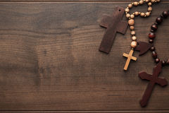 Crosses over brown wooden background Royalty Free Stock Photos