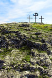 Crosses on a rocky hill under blue sky. Three crosses on a rocky mountain's peak under blue sky Stock Photo