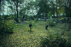 Crosses and tomb stones in autumn scene. Old graves on cemetery in Slovakia in fall. Spooky aged tombstones on grave yard Royalty Free Stock Image