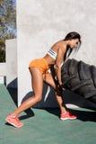 Crossfit与大轮胎的女孩锻炼 图库摄影