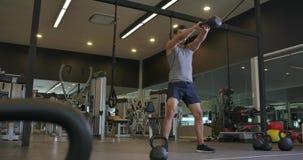 crossfit健身房的行使年轻白种人的人,人举的kettlebell 股票视频