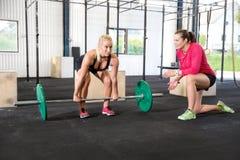 Crossfit妇女练习与个人教练员的举重 免版税库存图片
