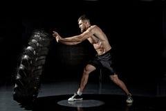 Crossfit训练-翻转轮胎的人 库存照片