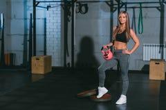 Crossfit,摆在与在健身房的桃红色哑铃的美丽的运动白肤金发的女孩 库存照片