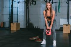 Crossfit,摆在与在健身房的桃红色哑铃的美丽的运动白肤金发的女孩 库存图片