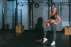 Crossfit,摆在与在健身房的桃红色哑铃的美丽的运动白肤金发的女孩 免版税库存照片