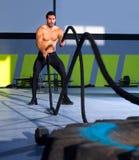Crossfit övar slåss rep på idrottshallgenomköraren royaltyfri fotografi