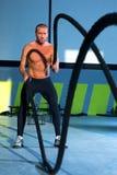 Crossfit övar slåss rep på idrottshallgenomköraren royaltyfri foto