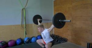 Μυϊκό άτομο που κάνει την άσκηση crossfit στη γυμναστική ισχυρός αθλητής crossfit στη μέση ένας βαρύς ανελκυστήρας αρπαγής στο α φιλμ μικρού μήκους