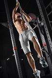 Crossfit athlete climbing up the rope in the gym. Muscular man doing exercise, naked torso abs stock photo