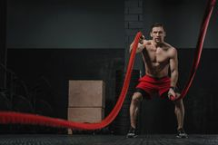 Crossfit athlete doing battle ropes exercise stock photos