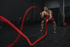 Crossfit battle ropes exercise during atlete training at the workout gym. Man training with rope. The sport motivation concept. Copy space