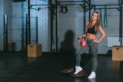 Crossfit, bella ragazza bionda atletica che posa con le teste di legno rosa nella palestra Fotografie Stock Libere da Diritti
