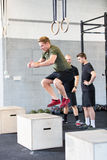 Crossfit box jump traning. A group trains at a crossfit center. One men do box jumps and two talking in the background Stock Image