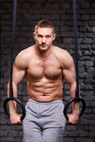 Crossfit core exercise. Determined man working out in gym pull ups with gymnastic rings for strength. Sportsman in the grey shorts. Abs. Portrait. Background Stock Images