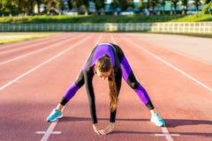 Crossfit de sportif de fille et agains de postures accroupies au coucher du soleil dans le stadi images stock