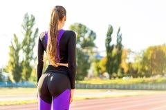 Crossfit de sportif de fille et agains de postures accroupies au coucher du soleil dans le stadi photos libres de droits