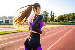 Crossfit de sportif de fille et agains de postures accroupies au coucher du soleil dans le stadi image stock