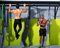 Crossfit dip ring and toes to bar man pull-ups men. Crossfit dip ring and toes to bar men pull-ups men workout at gym stock photos