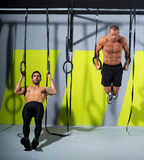 Crossfit dip ring two men workout at gym dipping. Exercise royalty free stock image