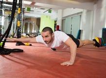Crossfit-Eignungsmann-Balanceneiter ups mit einem Bein und Arm Stockfotografie