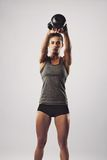 Crossfit female working out with kettle bell. Pretty young woman swinging kettle bell weight with both hands. Crossfit female working out on grey background Royalty Free Stock Image