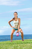 Crossfit fitness exercise woman. Lifting kettlebell during strength training exercising outdoors on grass by the ocean. Beautiful young fit fitness instructor Royalty Free Stock Photos