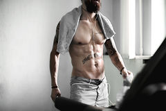 Crossfit fitness man training in gym. Muscular shirtless male torso with towel and tatoos. Wet sexy man torso with tatoo save the word. Man healthy lifestyle Royalty Free Stock Image