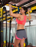 Crossfit fitness toes to bar man pull-ups 2 bars with TRX. Crossfit fitness toes to bar woman pull-ups 2 bars with TRX foot assistant Royalty Free Stock Images