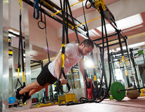 Crossfit fitness TRX push ups man workout. At gym Stock Photos