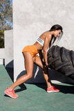Crossfit girl exercise with big tire. Beautiful young girl in bright sexy shorts with pretty athlete muscular body lift up big heavy tire with happy smile Stock Photography
