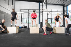 Crossfit group trains box jump. A group trains box jump with personal trainers at a crossfit center Stock Photos