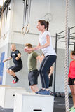 Crossfit group trains box jumps Stock Photos