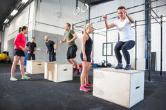 Crossfit group trains box jumps Stock Photo