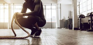 Crossfit guy training at the gym. Man sitting on his toes holding a pair of battle ropes for workout. Crossfit guy at the gym working out with fitness rope royalty free stock photography
