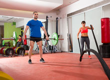 Crossfit gym weight lifting bar man woman battling ropes royalty free stock image