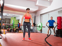 Crossfit gym weight lifting bar woman man battling ropes Stock Images
