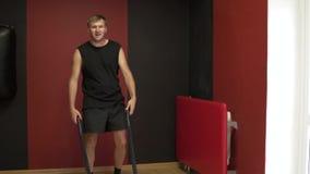 Crossfit i idrottshallen En man skakar hans muskler, genom att släpa ett rep lager videofilmer