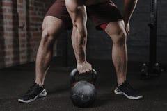 Crossfit idrottsman nen som övar med kettlebell på idrottshallen Stilig man som gör funktionell utbildning Övande genomkörare royaltyfri bild