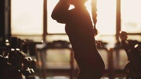 Crossfit Junger weiblicher Athlet Makung SitzenUPS mit Dummköpfen Frau, die in der Gymnastik ausarbeitet