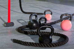 Crossfit Kettlebells ropes and hammer. In fitness gym floor Stock Photos