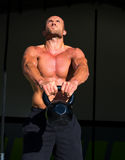 Crossfit Kettlebells swing exercise man workout. At fitness gym Stock Photos
