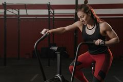 Crossfit kvinna som använder motionscykelen på idrottshallen arkivfoto